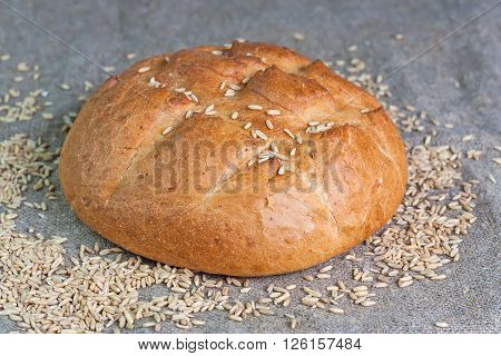 White bread and grains of wheat lying on a sacking
