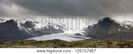 panorama of dramatic snowy icy frozen glacier in iceland with dark storm clouds