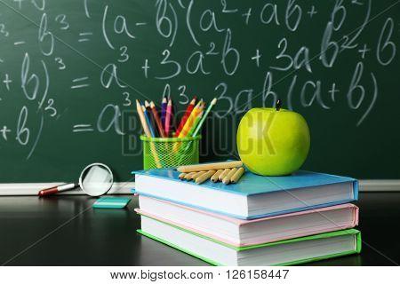 School books on desk near chalkboard