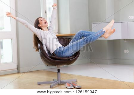 Woman sitting in armchair, arms outstretched