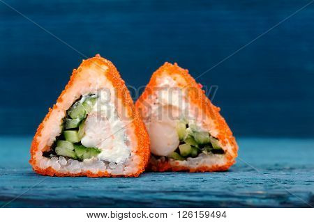 Triangular fusion rolls with orange tobiko roe cream cheese and cucumber on blue background copyspace