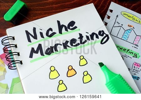 Notepad with sign niche marketing on a wooden background.