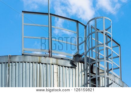 fragment of the metal tank or capacity with a ladder closeup against the cloudy sky
