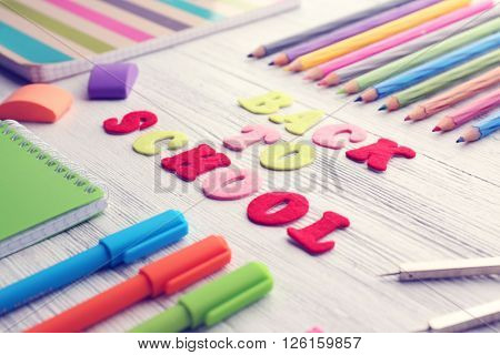 School set with back to school inscription, notebook on light wooden background