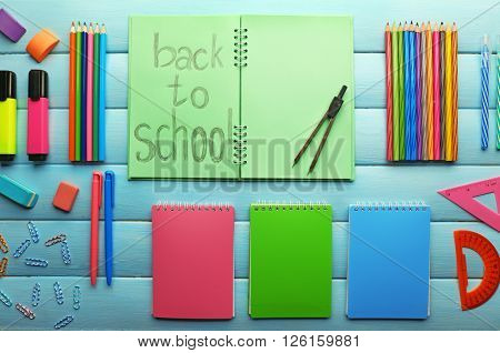 School set with back to school inscription in notebook and stationery on wooden blue background