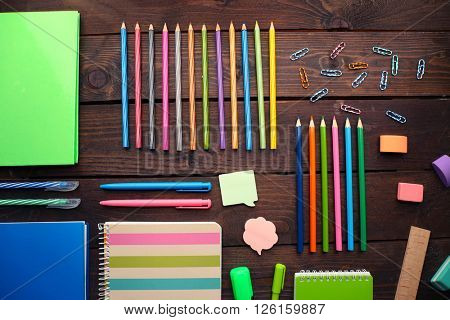 School set with notebooks, stickers and colored pencils on wooden background