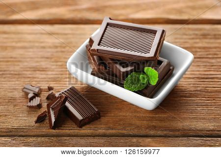 Chocolate with mint in a white bowl on wooden table.