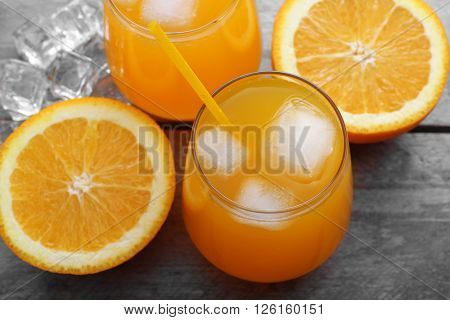Glasses of orange juice with ice on rustic wooden background
