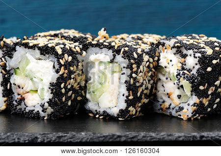 Homemade sushi rolls with black tobiko sesame seeds cucumber and cream cheese on blue background closeup
