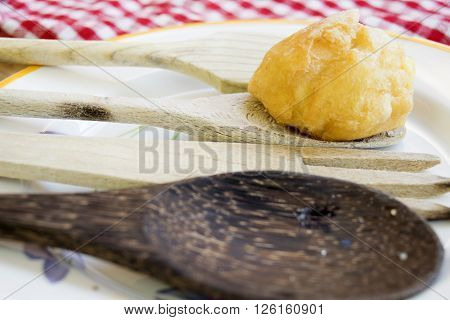 chantilly cream puff with icing sugare on wooden spoon