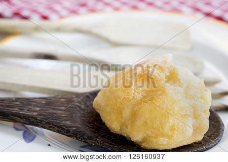 chantilly cream puff with icing sugar on wooden spoon