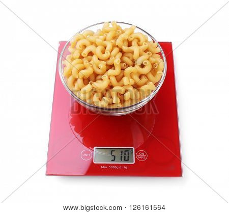 Bowl with dry pasta on digital kitchen scales, isolated on white