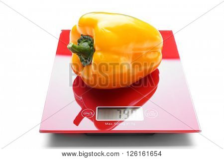 Yellow bell pepper on red digital kitchen scales, isolated on white