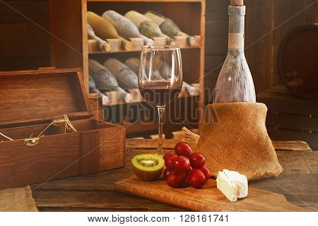 Aged bottle with glass of wine and fruits on wooden table