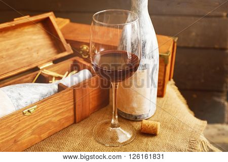Aged bottle with glass of wine on wooden background