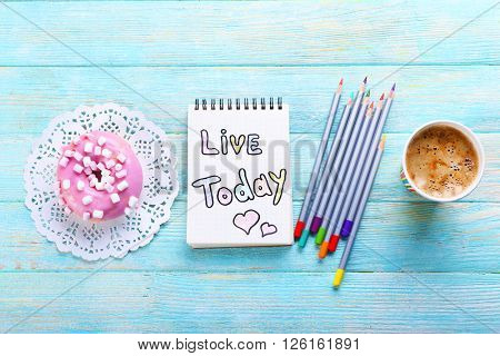 Cup of coffee with doughnut, crayons and note LIVE TODAY on wooden background