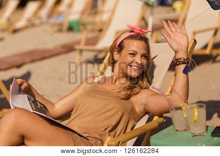 Attractive blond lying on a sunbed on a beach reading a magazine and waving to somebody