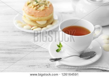 Cup of tea with nut cake on wooden background