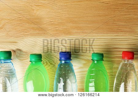 Bottles of water on the wooden table, top view