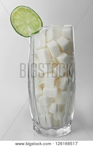 Highball glass with lump sugar and slice of lime on grey background
