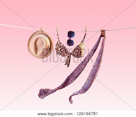 Beach outfit. Summer clothes and accessories stylish set. Fashion swimsuit bikini, sunglasses and hat on rope. Essentials creative tropical look. Ocean sea vacation concept on pink, vintage