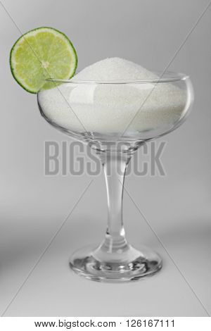 Margarita glass with granulated sugar and slice of lime on grey background