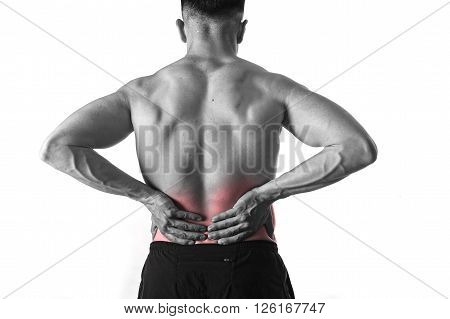 young muscular body sport man holding sore low back waist with hands suffering pain in athlete stress and health care concept isolated background black and white red spot injury