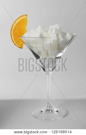 Martini glass with lump sugar and slice of orange on grey background