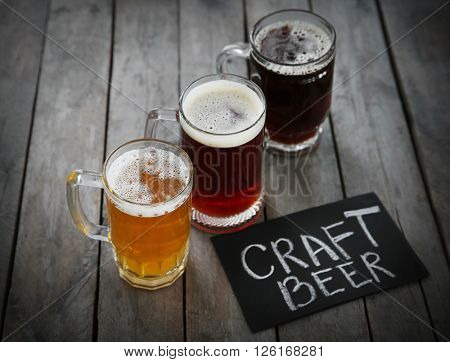 Glass mugs with different sorts of craft beer on wooden table