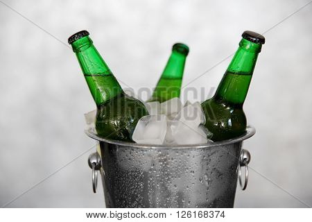 Green glass bottles of beer in ice-pail on grey background