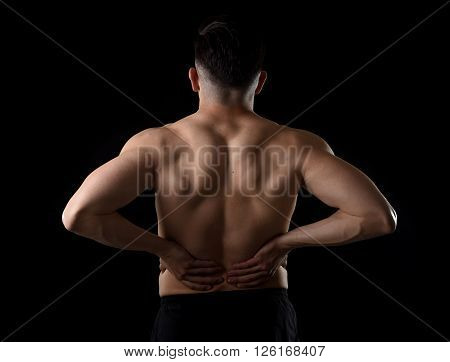 young muscular body sport man holding sore low back waist with his hands suffering pain in athlete stress and health care concept isolated on black background