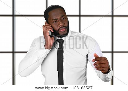 Worried afro guy with cellphone. Chief's phonecall on white background. Don't lose your hope. Big serious problems.
