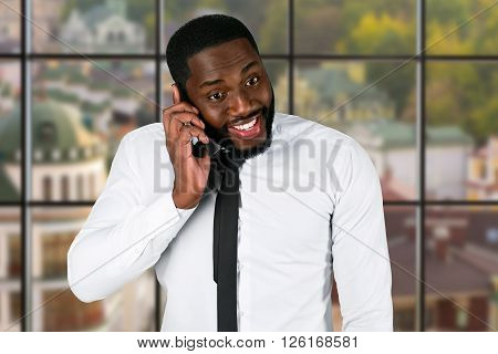 Excited black businessman with cellphone. City politician's phonetalk at daytime. Conversation with investors. Prove you're right.