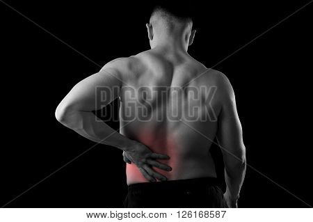 young muscular body sport man holding sore low back waist are suffering pain in athlete stress and health care concept isolated background black and white with red spot injury