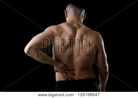 young muscular body sport man holding sore low back waist with his hand suffering pain in athlete stress and health care concept isolated on black background