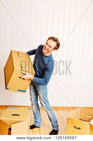 Smiling young man carrying many cardboard boxes