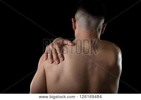 young muscular sport man holding sore shoulder with hand touching or massaging in workout stress body pain and health problem isolated on black background