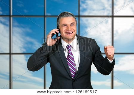 Smiling mature businessman with phone. Happy boss on sky background. Monthly income has increased. One step closer to victory.