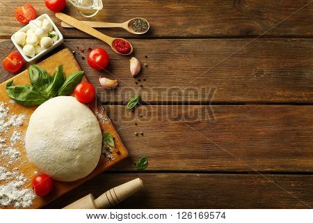 Pizza dough with tomatoes, olive oil, green basil and Mozzarella on wooden background
