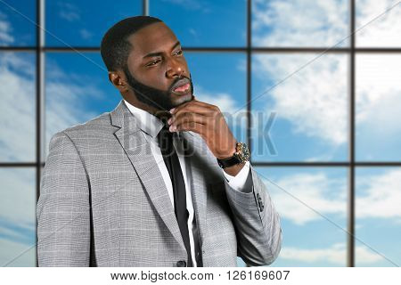 Thoughtful black businessman in suit. Pensive manager on sky background. In search of bright idea. He needs inspiration.