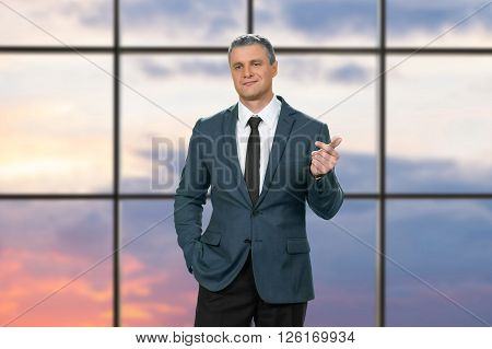 Cocky adult businessman wearing suit. Proud man on sunrise background. I'd like to know more. We need to talk.