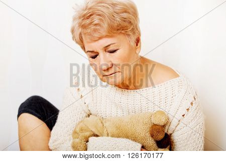 Elderly woman with depression sitting in the corner