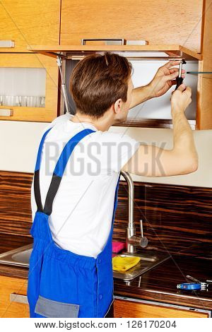 Handyman fixing kitchen's cabinet with screwdriver