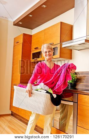 Senior woman carrying laundry basket in kitchen