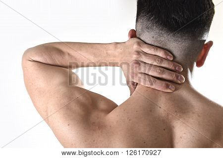 back of young muscular sport man holding sore neck with his hand and touching or massaging cervical area suffering body pain in spine and back health problem isolated on white background