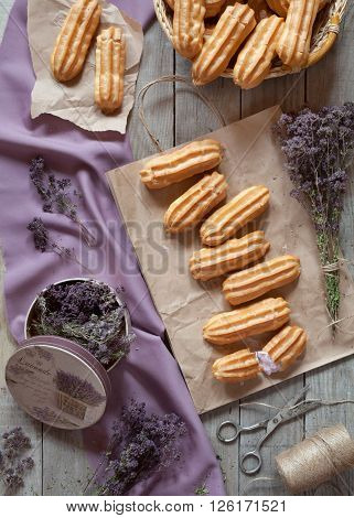 Eclairs or profiterole pastry dessert filled with whipped cream on baking sheet background. Top view, provence rustic style.