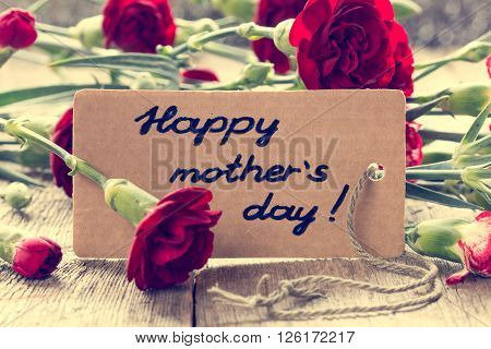 Mothers day card with carnations on wooden board. Vintage filter.