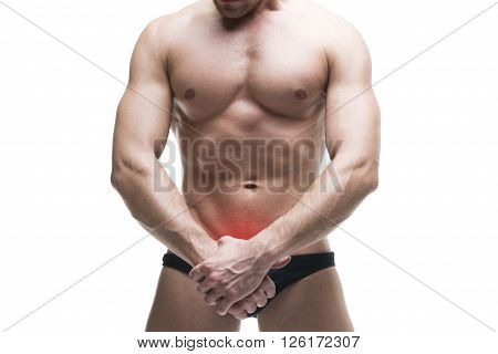 Man with pain in the prostate. Muscular male body. Handsome bodybuilder posing in studio. Isolated on white background with red dot. Middle part of the body