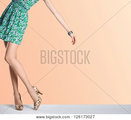 Woman in fashion dress and high heels. Female sexy long legs, stylish green flower sundress and summer glamour shoes on orange. Unusual creative elegant walking out outfit, people.  Vintage, copy space
