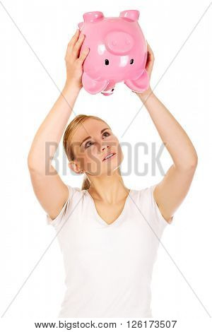 Sad young woman shaking piggybank for coins